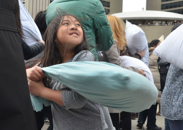 people in the midst of a large pillow fight at Nathan Phillips square in celebration of international pillow fight day - a young girl swings a pillow