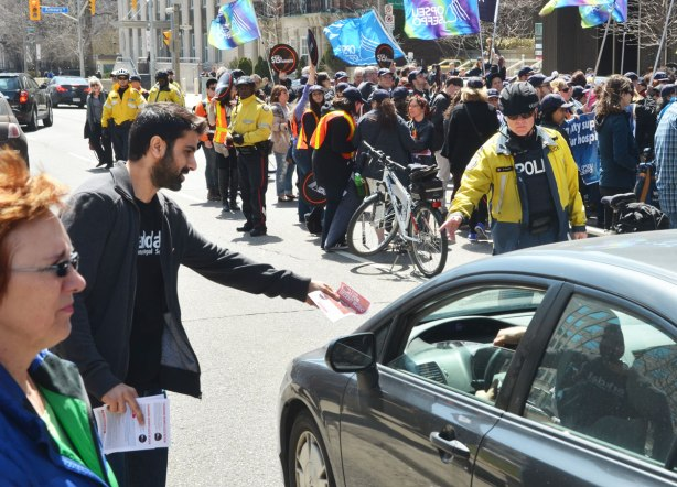 a young man is handing out leaflets to drivers of cars as they past a rally for Fight for 15 anf Fairness, a protest for decent working conditions and wages