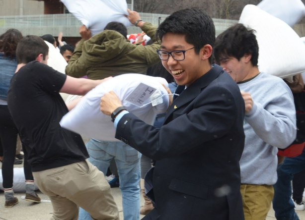 asian young man in suit and tie and glasses is laughing and smiling as he swings a pillow in a pillow fight outdoors with many people