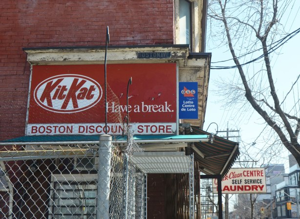 Side of a convenience store with an ad for KitKat, have a break, is painted on the side. Boston Discount Store on the corner of Queen St. East and Boston Ave