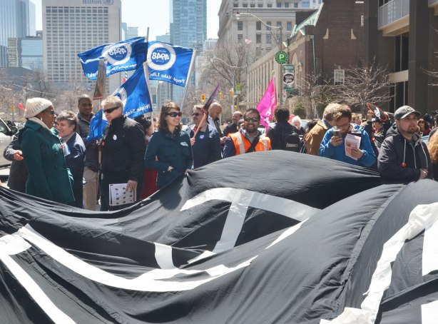 "photographs taken at a rally and protest in support of a $15 minimum wage, The Fight for 15 and fairness - large group of people standing around holding a black banner with the words ""Make it fair"" in large white letter."