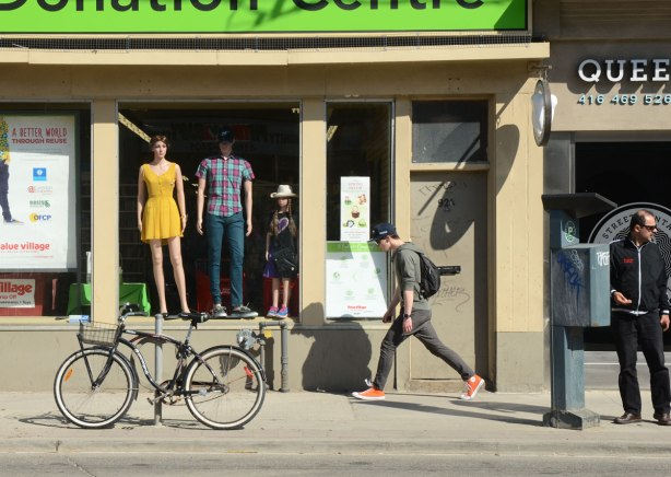 A young man walks past the Value Village Donation Center that has a large window with 3 mannequins in it. A bike is parked in front.