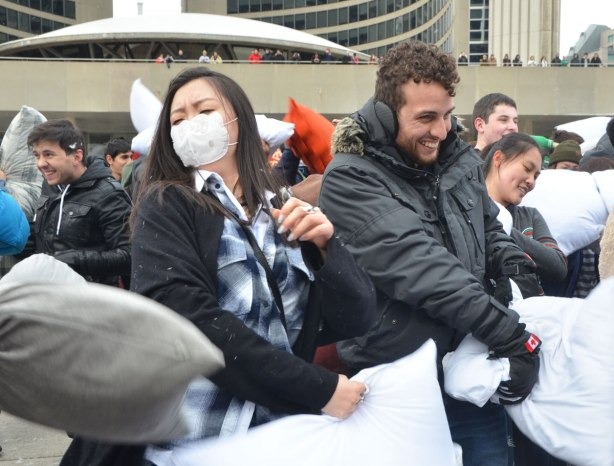 people in the midst of a large pillow fight at Nathan Phillips square in celebration of international pillow fight day - a young man with earmuffs and a woman wearing a face mask