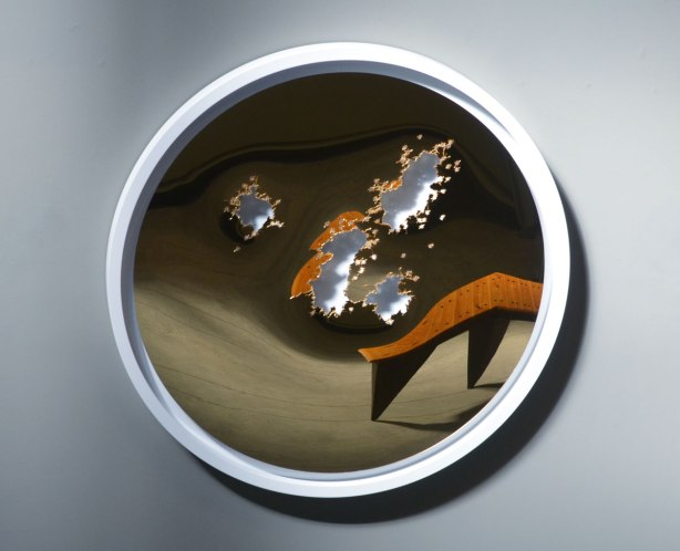 an artwork by Brendan McNaughton of a slightly concave mirror but with a few torn holes in it. A bench is reflected in the mirror but because the mirror isnt't flat, the bench is distorted.