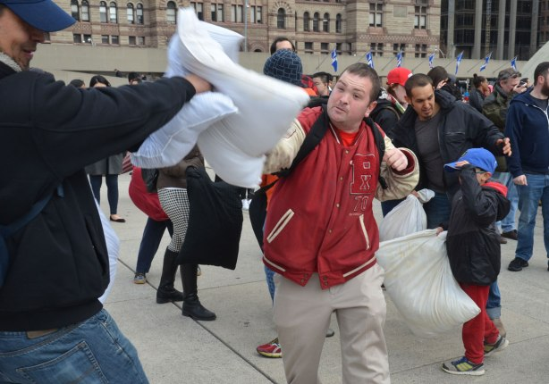people in the midst of a large pillow fight at Nathan Phillips square in celebration of international pillow fight day -