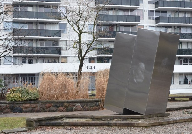 A sculpture that is just two rectangular metal boxes upright, joined together and on a slight angle. In a small park in front of an apartment building at 141 Davisville in Toronto