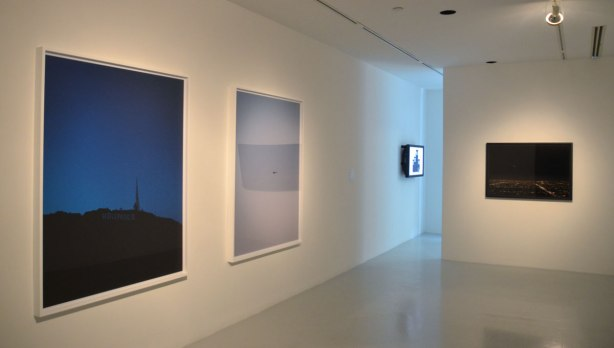 4 pictures hanging in a contemporary art gallery. One is a picture of the Hollywood sign taken just after dark, the next is a grey sky with a tiny dot of a helicopter in the middle, the third is too far away to discern, and the last is a picture of Los Angeles at night taken from a helicopter