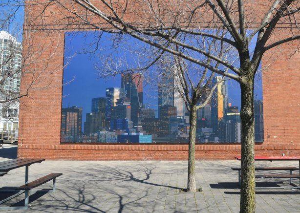 A photograph by Aude Moreau of the Toronto skyline as the sun starts to set, sunlight reflected off the buildings, darkening blue sky. The picture is mounted on an exterior wall and there is a tree in front of it as well as a couple of picnic tables