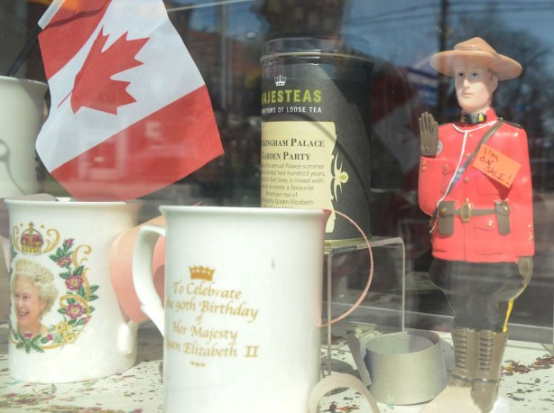 items in a store window. A Canadian flag, a mountie figurine that waves, two mugs featuring Queen Elizabeth and a container of tea.