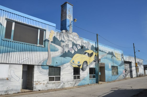 mural on the side of West York motors on St. Clair West - looking down the length of the mural including the narrow chimney on which the CN TOwer is painted.