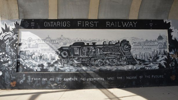 """mural in black, white, and grey about the first railway in Ontario, 1853, that was built here, and where the railway still runs as the GO line to Aurora - a painting of an old locomotive with the words 'Ontario's First Railway' on the top of the mural and the words: """"from one age to another. The locomotive was the machine of the future. """" at the bottom"""