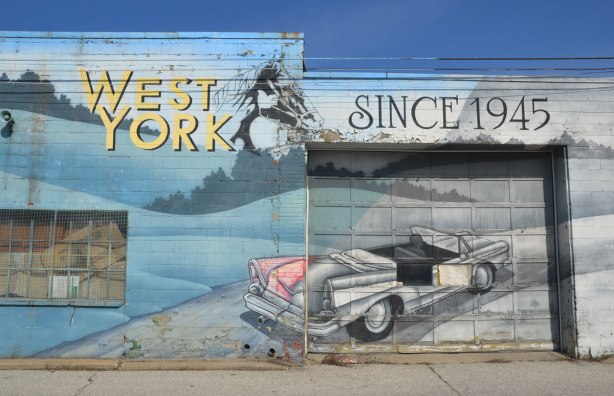 "mural on the side of West York motors on St. Clair West - the part of the mural with the words ""West York since 1945"" also an old convertible with its door open and top down."