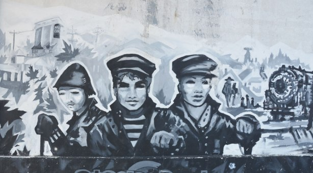mural in black, white, and grey about the first railway in Ontario, 1853, that was built here, and where the railway still runs as the GO line to Aurora - three railway workers in jackets and caps