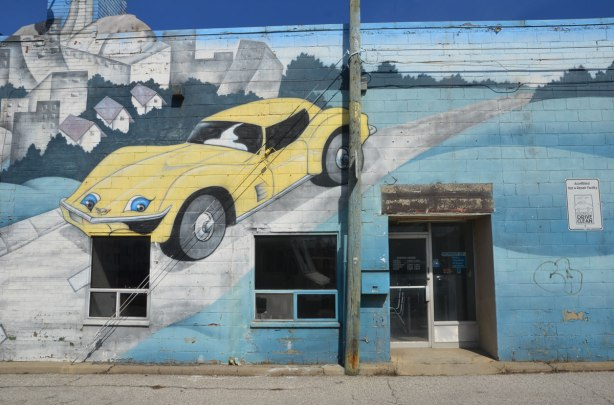 mural on the side of West York motors on St. Clair West - a yellow sports car is painted on the wall near the entrance to the building