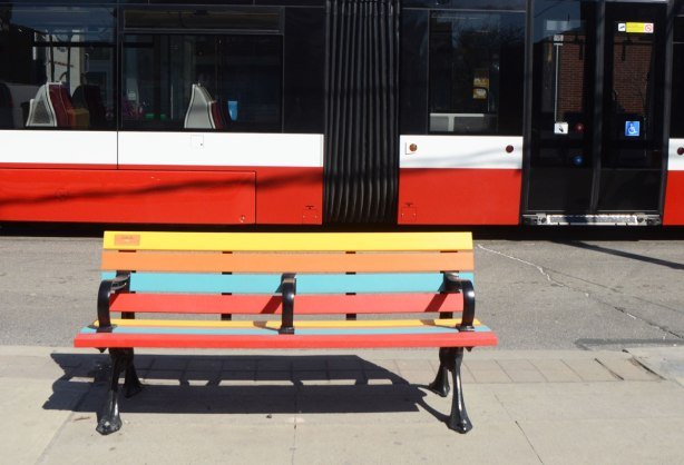 The side of a new TTC streetcar behind a striped bench on a sidewalk