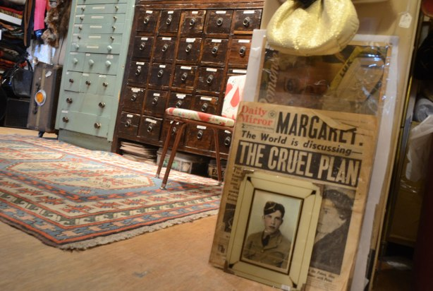 old photograph of a man in uniform, a front page of the Daily Mirror newspaper, more drawers, all in a store filled with vintage items.