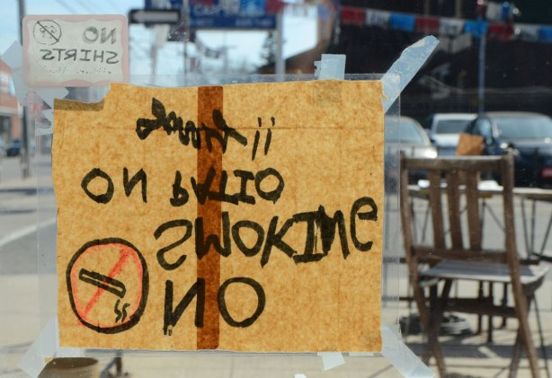 A no smoking sign written on a piece of paper that is upside down, as viewed from the other side of the window. Looking out onto a patio.
