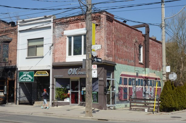 Two brick stores on Queen St East, two storey. One is the OKOK diner with a mural on the side of it that features an older version TTC streetcar.