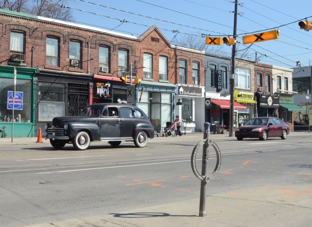 A black vintage car drives by on Queen St East