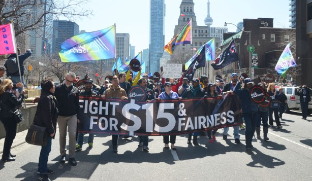 photographs taken at a rally and protest in support of a $15 minimum wage, The Fight for 15 and fairness - members of the OPSEU union arrive at the rally waving flags, holding signs, and carrying a banner that says Fight for fifteen dollars and fairness""