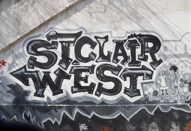 mural in black, white, and grey about the first railway in Ontario, 1853, that was built here, and where the railway still runs as the GO line to Aurora - the words St. Clair West in large letters
