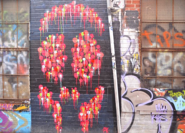 alley laneway streetart by artist PK of a stylized face, or could be a skull - red and yellow drippy blobs on a black background