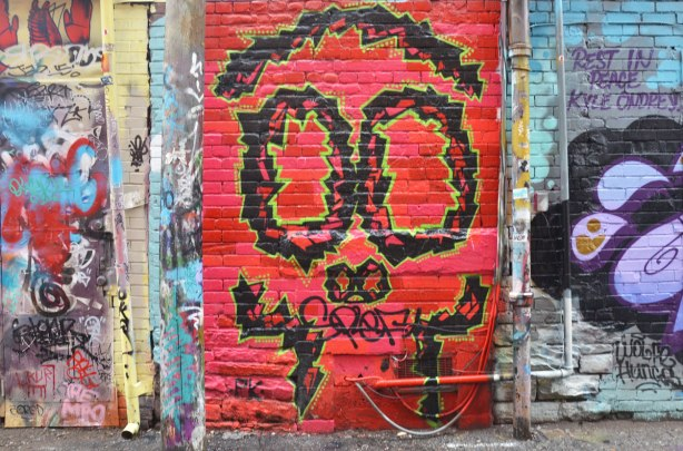 alley laneway streetart by artist PK of a stylized face, or could be a skull - black outlines of top of skull, eyes, nose holes, and sort of teeth, on red background