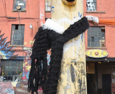 an old scruffy yellow metal pole in an alley has a black knitted scarf tied around it. There is a bit of snow on the scarf.