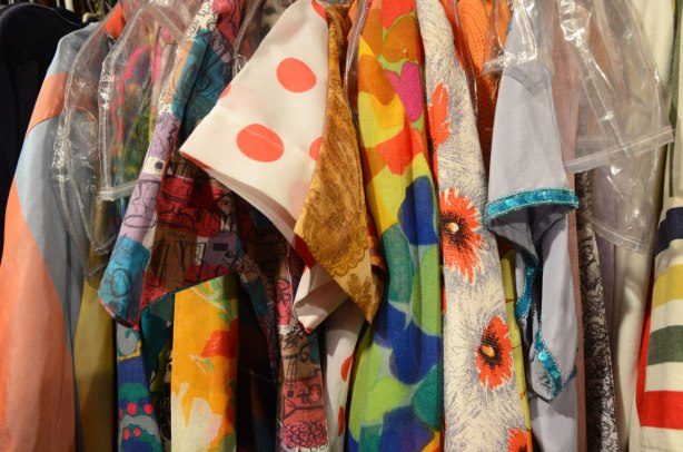 sleeves of colourful shirts and blouses hanging on a rack. Orange polka dots, red poppies, wild prints, all vintage clothing