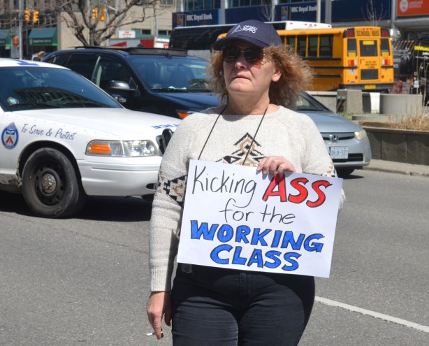 "photographs taken at a rally and protest in support of a $15 minimum wage, The Fight for 15 and fairness - older woman in a blue baseball cap and smoking a cigarette holds a sign that says ""Kicking ass for the working class"""