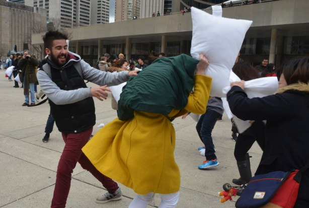 young people participating in a large outdoor pillow fight