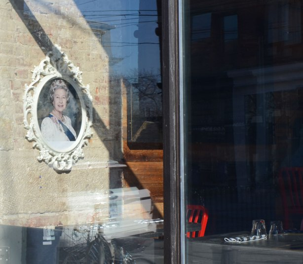 A picture of Queen Elizabeth hangs on a wall in a cafe, seen through the window with reflections of the sky. There are red chairs in the cafe