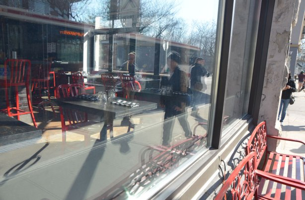 reflections in the window of a cafe. Red benches are outside the window. People, TTC streetcar