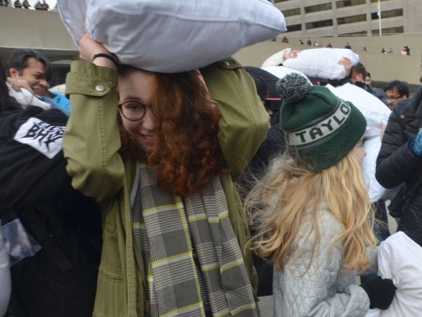 people in the midst of a large pillow fight at Nathan Phillips square in celebration of international pillow fight day - a woman with long red hair hides under her pillow as she walks through a crowd