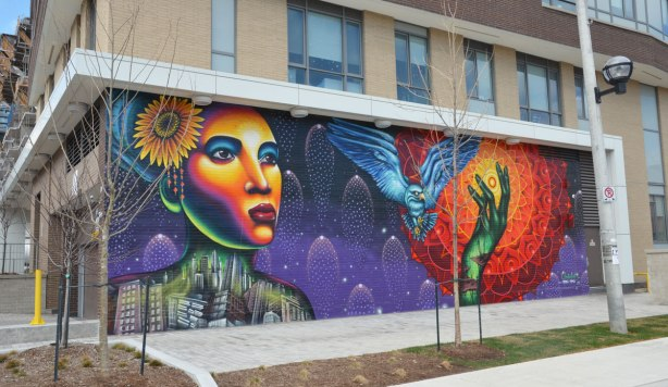 mural painted by Shalak Attack and Bruno Smoky in Regent park Toronto, showing a brightly coloured woman;s face, with a flower in her hair and her body (from the shoulders up) made of buildings in a jumble as well as a blue owl (large bird) in flight, passing in front of the sun that is represented by circles of orange and red radiating out from the bright yellow center. A green hand is reaching up towards the sun