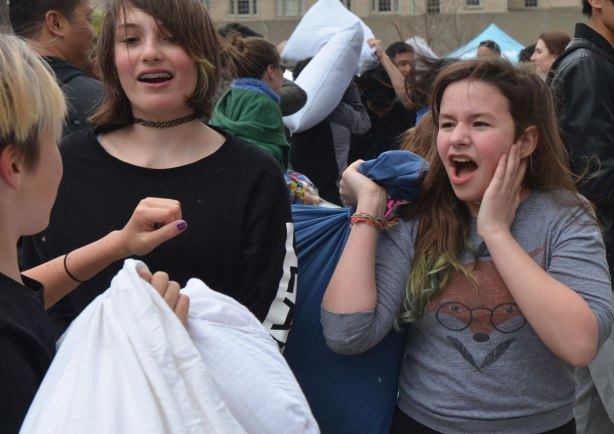 a young woman holding a pillow and screaming at another young woman