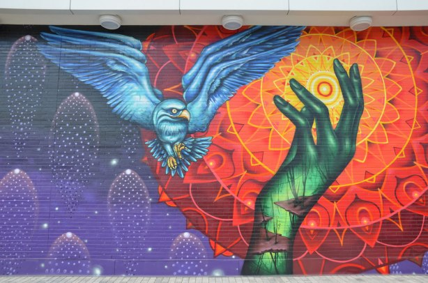 close up of a mural by Shalak Attack and Bruno Smoky of a blue owl (large bird) in flight, passing in front of the sun that is represented by circles of orange and red radiating out from the bright yellow center. A green hand is reaching up towards the sun