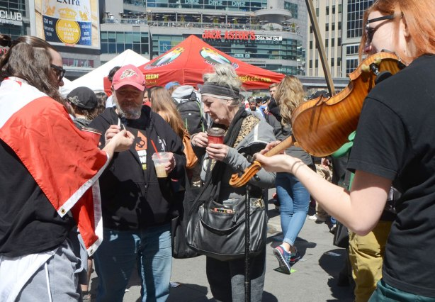 three older people share joints while a red haired woman plays a violin, Dundas Square, 420 day event