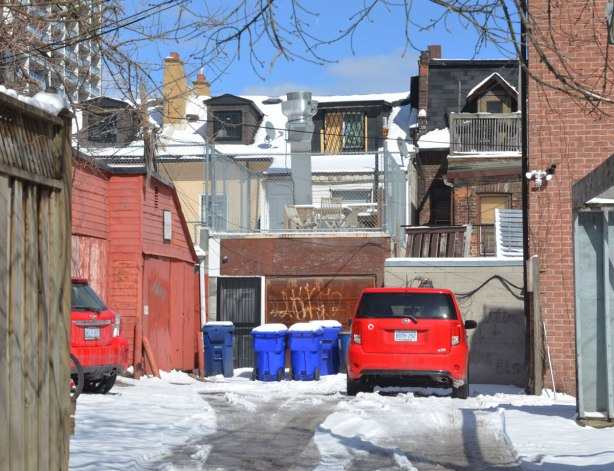 backyard, entrance off alley, little red car parked on snow covered parking lot. blue sky, backs of two storey houses