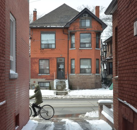 looking down a narrow lane to a large two stroey red brick house across the street, a woman is riding past on a bicycle.. winter scene