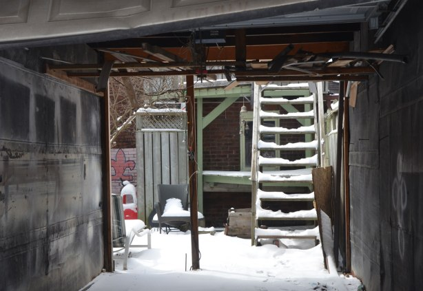 looking through a backless garage where the garage door is open. The garage is empty. you can see the backyard, covered in snow as well as snow covered steps leading up the second storey