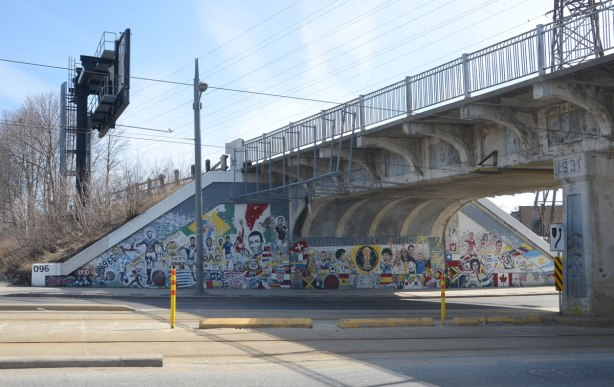 mural on a railway bridge underpass that has a soccer theme. Flags of different countries, soccer players, words,