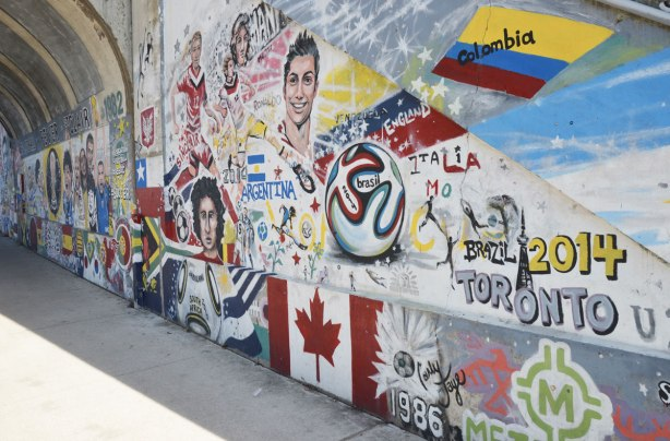 part of a mural with a soccer theme with words that say Football Fever St. Clair 1982. also with pictures of football players and flags from different countries.