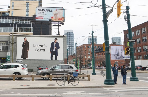 view from the NE corner of Spadina and Richmond streets. a small parking lot is directly across the street, two large billboards loom over the lot. Once is for Lorne's coats showing two people wearing coats. The other is for Maple flavoured iced capp at Tim Hortons.