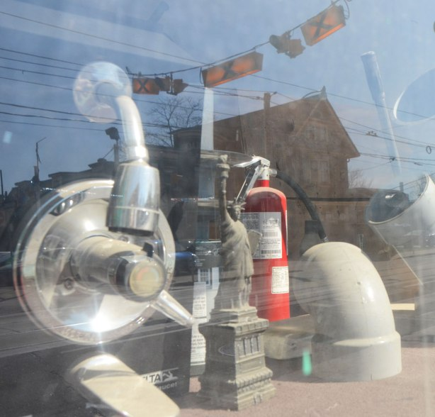 Looking into a store window. A small model of the Statue of Liberty, a fire extinguisher, a pump and some PVC pipe parts. Reflections of sky, buildings from across the street and a yellow set of lights above a cross walk.
