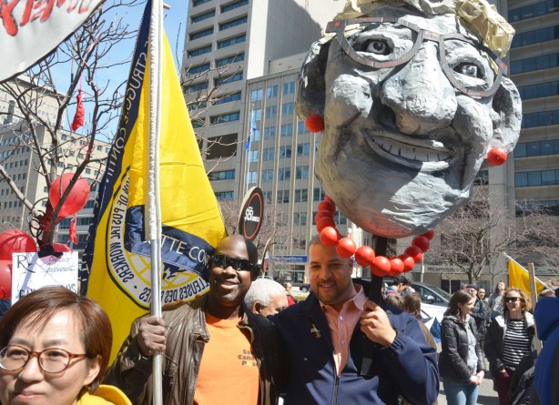 photographs taken at a rally and protest in support of a $15 minimum wage, The Fight for 15 and fairness - two men standing together, one with a United Steelworkers flag and the other with a large effigy of Kathleen Wynne's head held above his own head