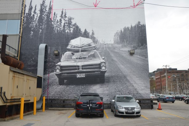 A very large black and white photograph from the 1960's of a car on a two lane road with pine trees on either side. There is a boat tied to the roof of the car. The photo is on the side of the Globe and Mail building with cars parked around it.