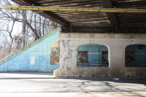 A small section of the railway bridge over Queen St. East near De Grassi. The far wall is painted light blue and there are picture of animals on it.