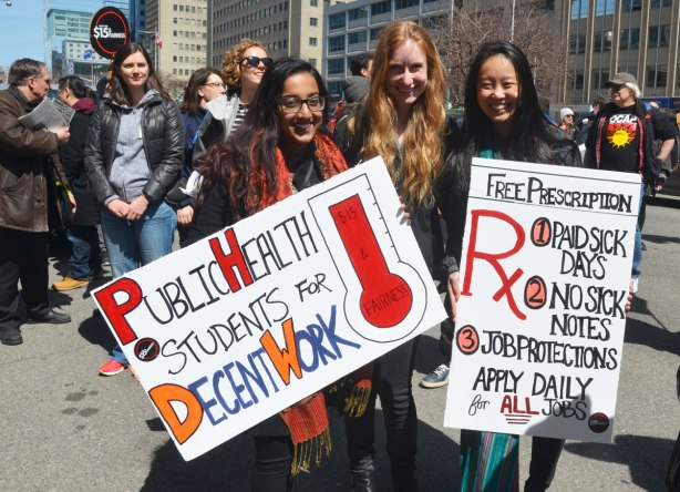 "photographs taken at a rally and protest in support of a $15 minimum wage, The Fight for 15 and fairness - three female students standing together holding signs. One says ""Public Health students for decent work"" and the other says "" Free prescriptions, no student debt,"