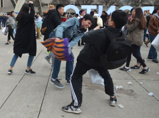 young men swinging pillows at each other in a large pillow fight